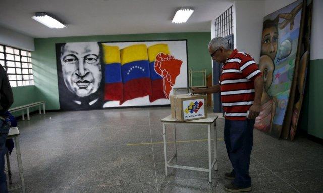 Ciudadano deposita la papeleta en la urna luego de haber votado en 6-12-2015. Al fondo un mural con la cara de Chávez dentro de la sala de votaciones