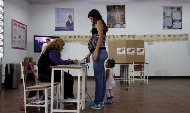 Una mujer embarazada registra su huella dactilar antes de votar. Caracas